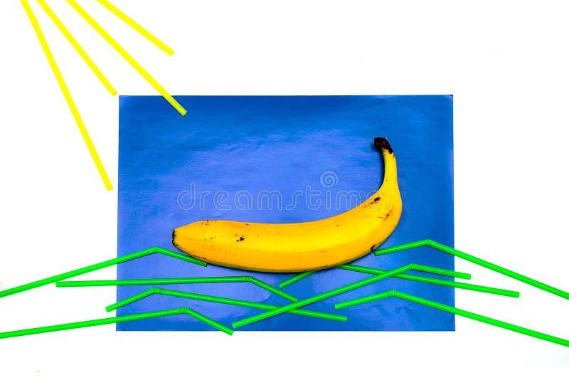 Banane, Saft mit Stroh auf einem blauen Hintergrund Das Stroh liegt auf einem blauen Hintergrund in Form von einem Segel und Well lizenzfreie stockbilder