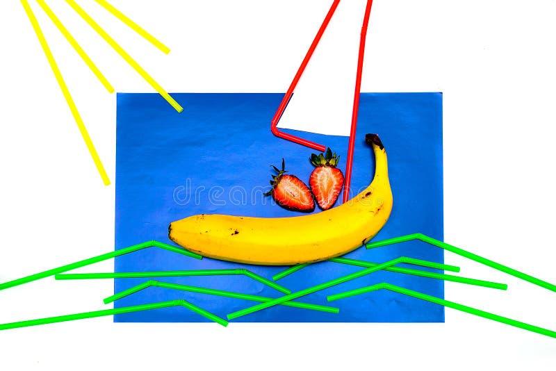 Banane, Saft mit Stroh auf einem blauen Hintergrund Das Stroh liegt auf einem blauen Hintergrund in Form von einem Segel und Well stockbilder