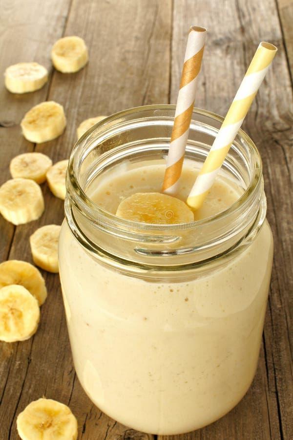 Banane Smoothie im Glas auf Holz stockfotos