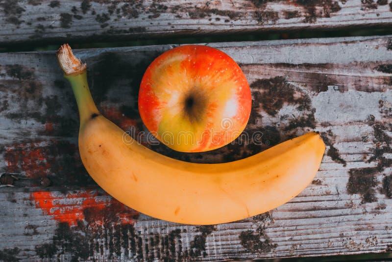 Banane und Apfel auf alter Tabelle stockfotografie