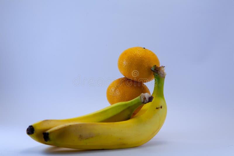 Banane und Gruppe Tangerinen, Mandarinen lokalisiert über Weiß lizenzfreie stockfotografie