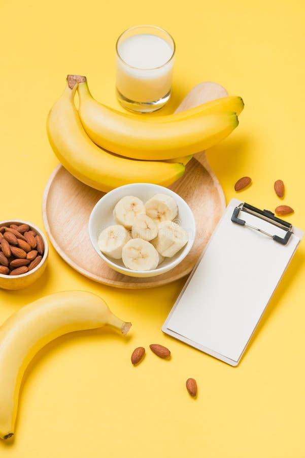 Banane und Milch auf gelbem Papierhintergrund mit leerem Klemmbrett stockfotos