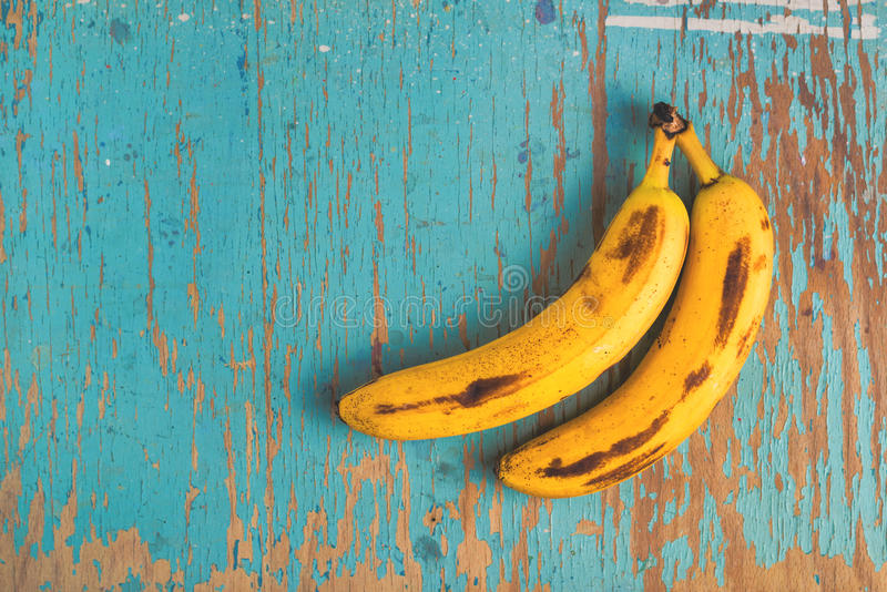 Bananen auf rustikaler Tabelle lizenzfreie stockfotos