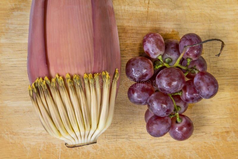Bananen-Blüte und purpurrote Traube auf dem Holz lizenzfreie stockbilder