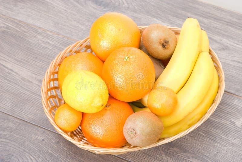 Bananen, citroenen en sinaasappelen in een stromand stock afbeeldingen
