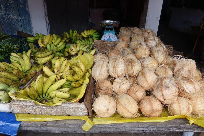 Bananen en kokosnoten op de teller bij een lokale markt van fruit en groente royalty-vrije stock foto's