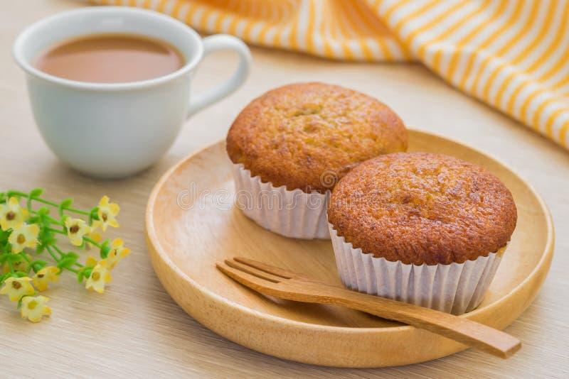 Bananenkleiner kuchen auf hölzerner Platte und Tasse Kaffee lizenzfreie stockfotos