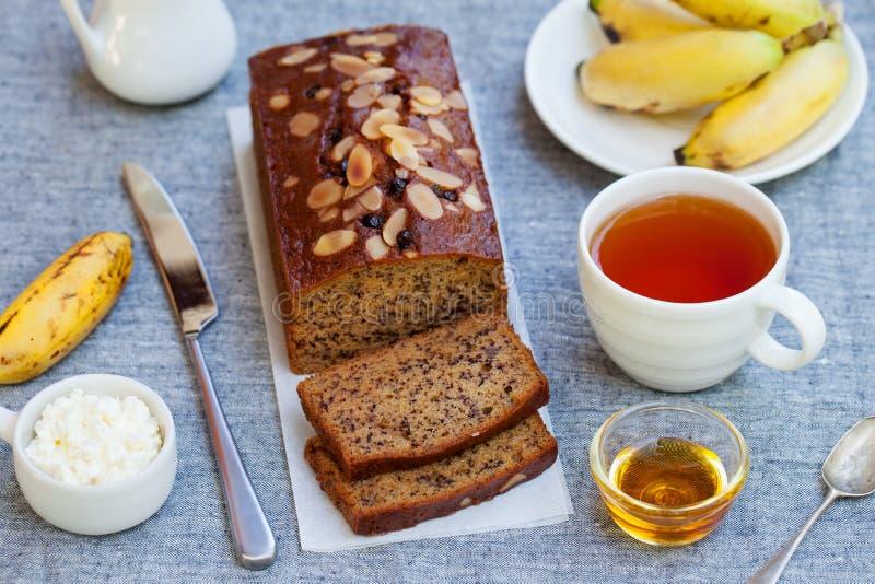 Bananenkuchen, Laib mit Schokolade und Tasse Tee auf grauem Textilhintergrund lizenzfreies stockbild