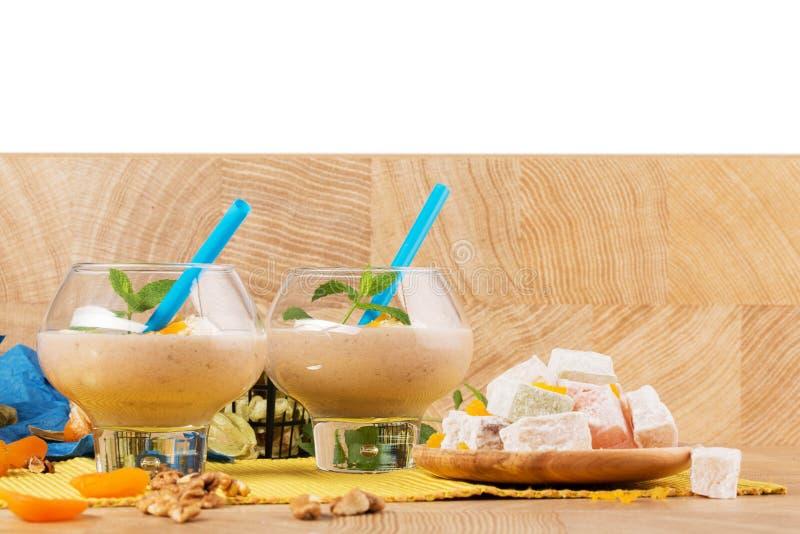 Bananenmilchshaken lokalisiert auf einem weißen Hintergrund Exotische Nachtische Türkische Freude und Smoothies auf einer Tabelle stockfotos