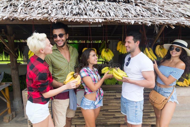 Bananer för folkgruppköpande på traditionell marknad för gata, ung man och kvinnahandelsresande arkivfoto
