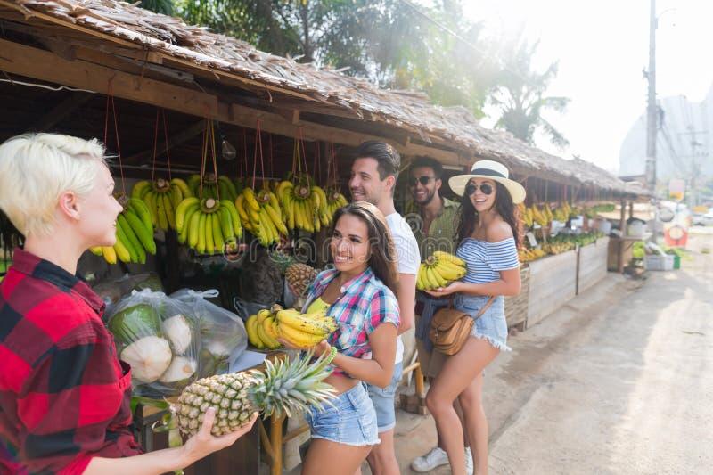 Bananer och ananors för folkgruppköpande på traditionell marknad för gata, ung man och kvinnahandelsresande royaltyfri bild