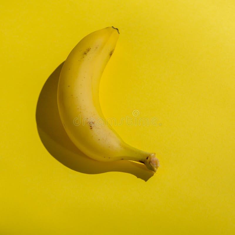Bananer p? gul bakgrund Popkonst Ljust ljus, stark skugga Minimalisten utformar royaltyfria bilder