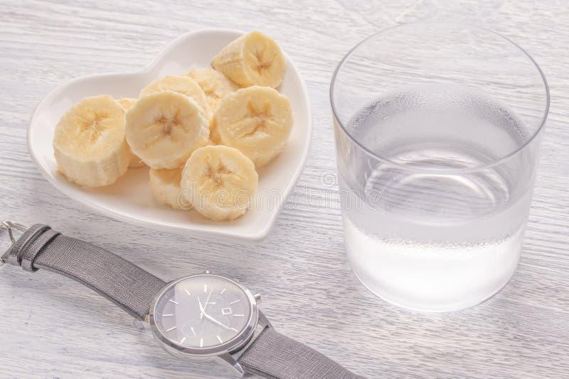 Bananes coupées en tranches et entières D'un plat blanc Sur la vieille table en bois Verre de Misted avec de l'eau clair Fermez-v photos stock