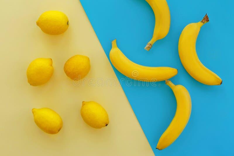 Bananes et citrons jaunes sur le papier bleu lumineux, configuration à la mode d'appartement photographie stock