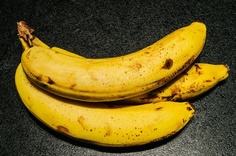 Bananes légèrement brunies sur le fond noir texturisé photographie stock