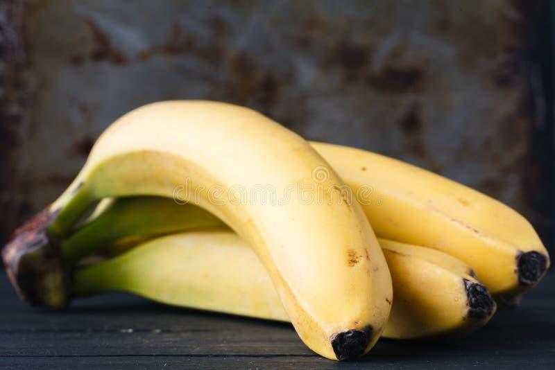 Bananes mûres jaunes sur la table rustique photos stock
