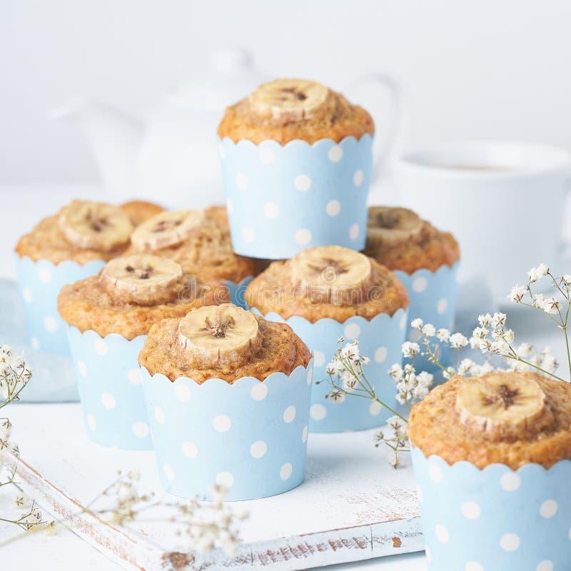 Bananmuffin, muffin i blåa kakafall skyler över brister, sidosikten Morgonfrukost på den vita konkreta tabellen royaltyfri fotografi