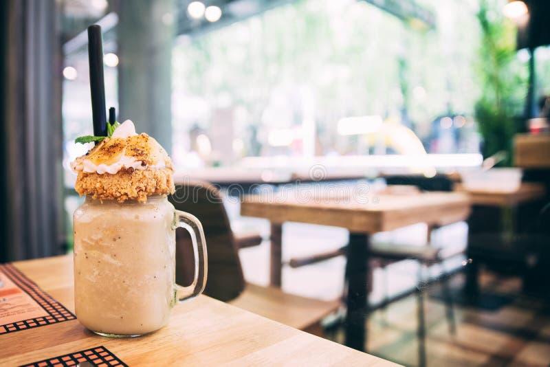 Bananowa milkshake polewa z jabłkiem rozdrobni i pokrajać banany na drewnianym stole fotografia royalty free