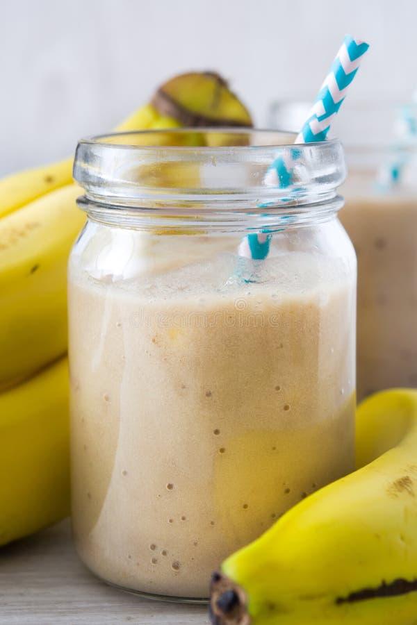 Bananowi smoothies na białym drewnianym tle zdjęcie stock