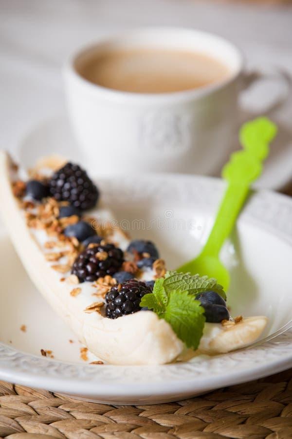 Bananowy deser z granola, organicznie czarnymi jagodami i świeżą mennicą na białym talerzu z jasnozieloną łyżką, zdjęcie royalty free