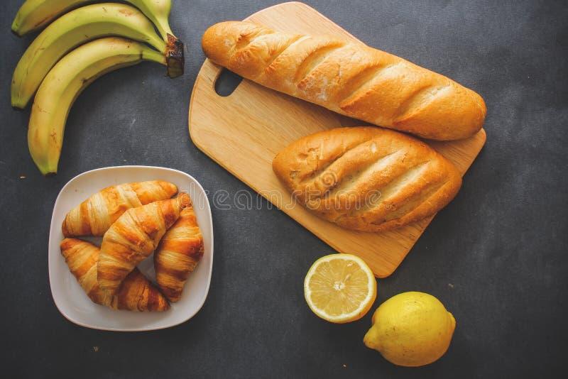 Banany, cytryny, jeden cięcie, bochenki biały chleb na desce i cztery croissants na srebnym półmisku na ciemnym tle, zdjęcia royalty free