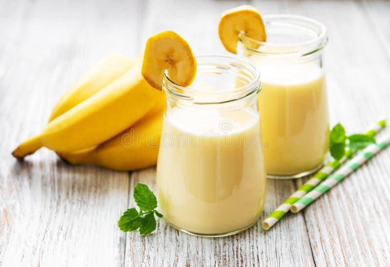 Bananyoghurt och nya bananer arkivbild