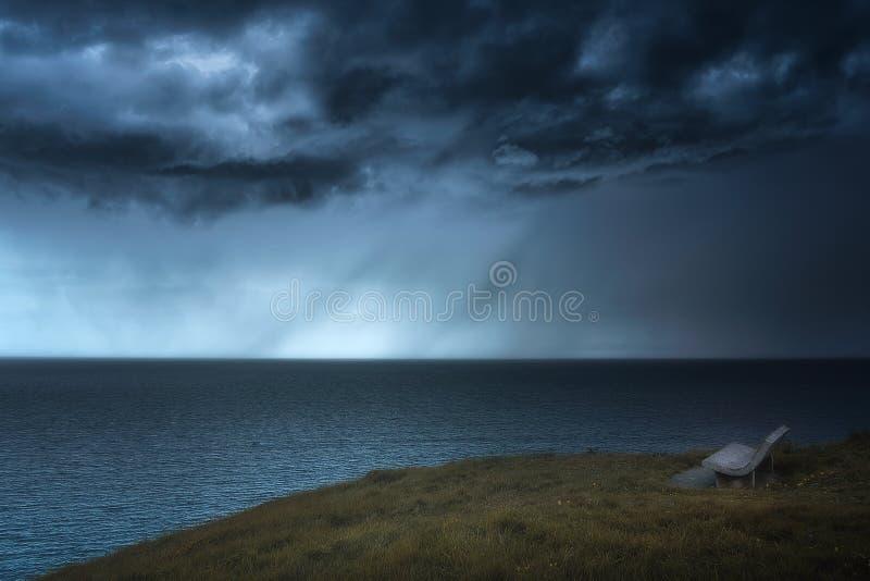 Banc avec la pluie et les nuages orageux image libre de droits