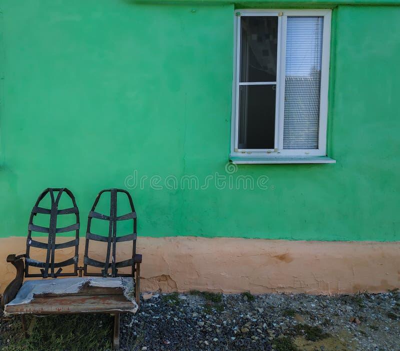 Banc contre un mur vert photo stock