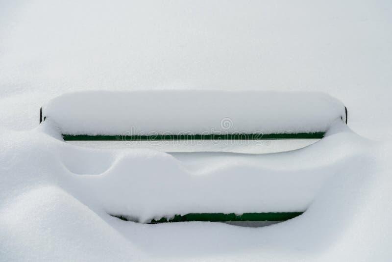 Banc de parc couvert dans la neige d'hiver photographie stock