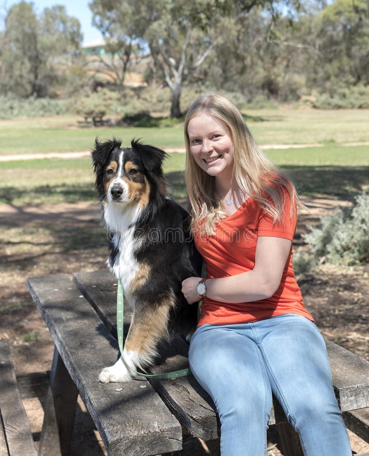 Banc de parc de jeune femme et de chien photographie stock libre de droits