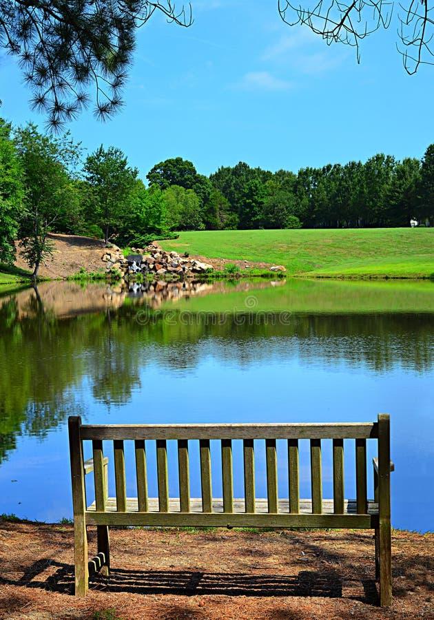 Banc de parc sur un étang photos libres de droits