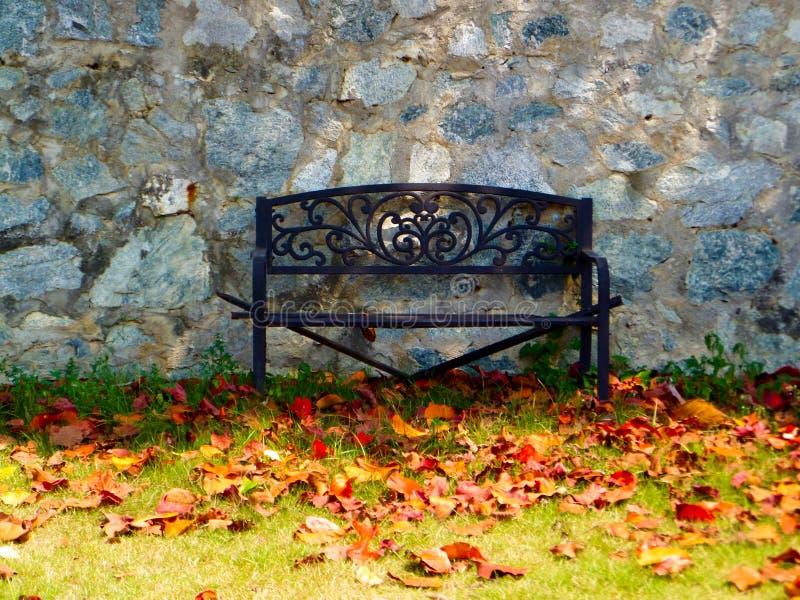 banc de rouille dans le mur en pierre de granit de jardin images stock