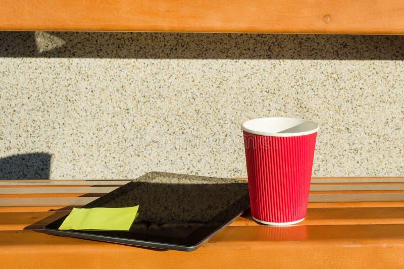 Banc de rue, comprimé avec l'autocollant collé, tasse de café photo stock