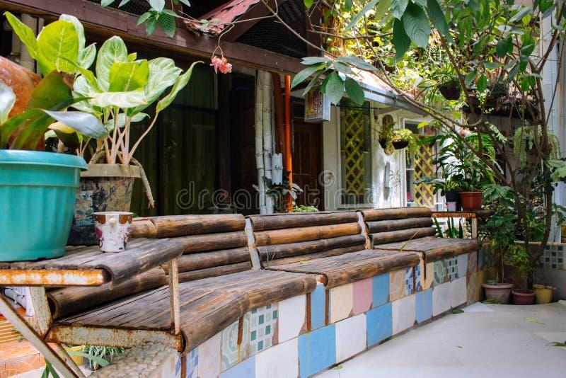 Banc en bois avec des usines et des pots de fleur dans le patio tropical, Asie, Philippines Décoration de terrasse dans le villag image libre de droits