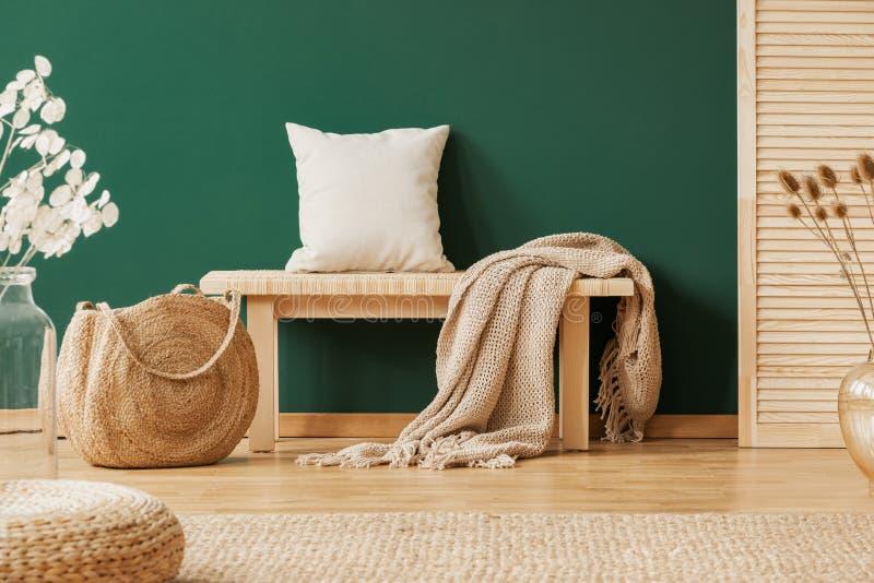 Banc en bois avec le tapis et l'oreiller beiges à côté du sac à main de paille, l'espace de copie sur le mur vert vide photographie stock