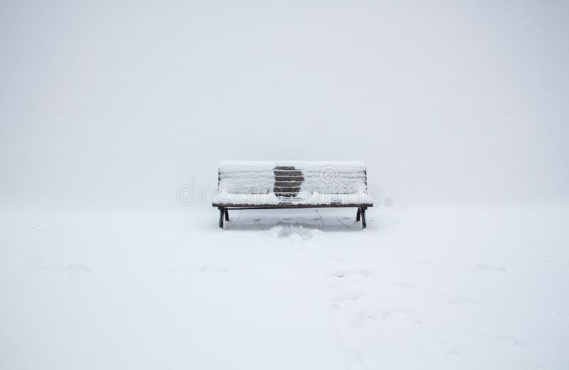 banc en bois couvert de neige avec une empreinte de quelqu'un image stock