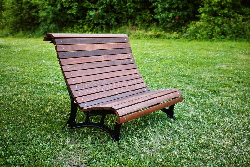 Banc en bois de Brown sur les herbes d'un parc public image stock