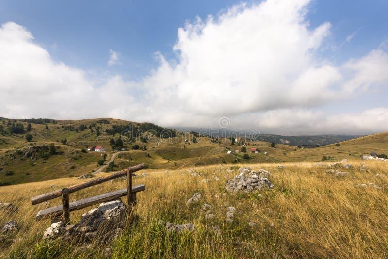 Banc en bois devant le beau paysage rural avec de petits villages en parc national de Durmitor près de Zabljak, Alpes de Dinaric, photos libres de droits