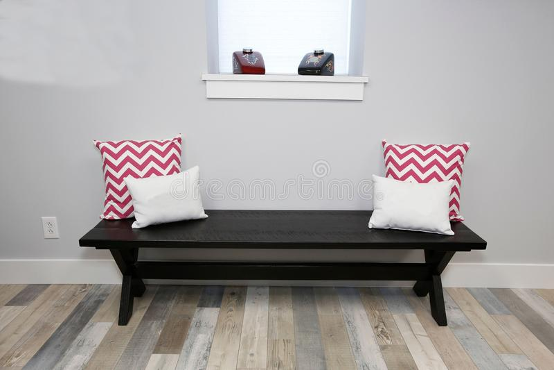 banc en bois et oreillers parquetants en bois là-dessus près de la fenêtre photographie stock libre de droits