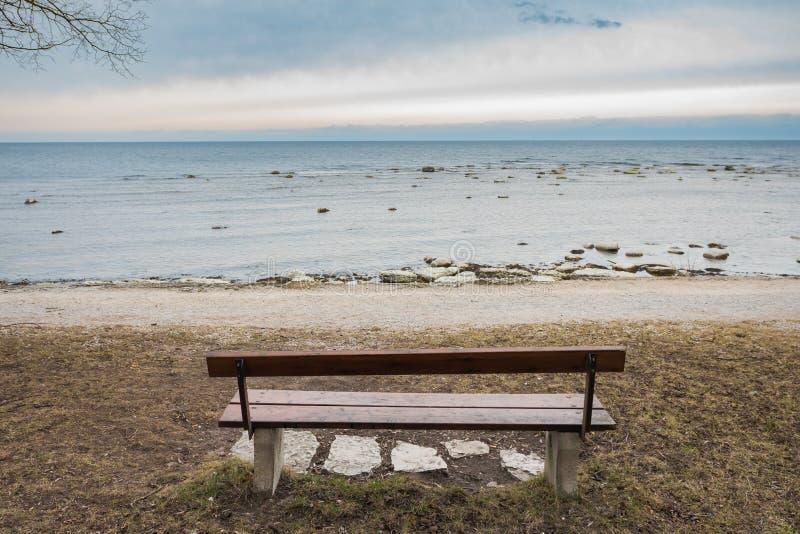 Banc en bois isolé sur la mer d'automne avec le ciel nuageux photo libre de droits