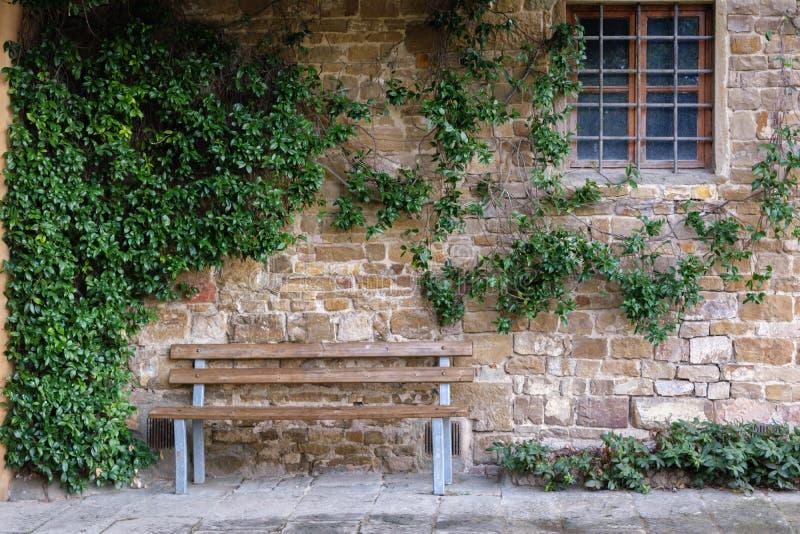 Banc en bois près d'un mur habillé de lierre de grès et d'une fenêtre fer-barrée image stock