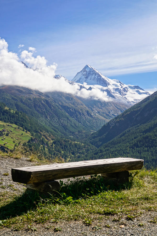 Banc en bois rustique donnant sur les Alpes suisses images stock