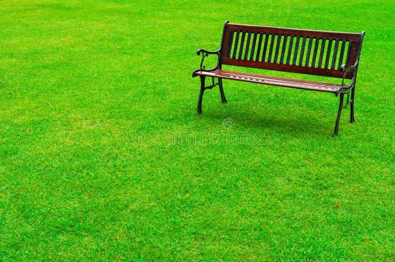 Banc en bois sur un parc herbeux images stock