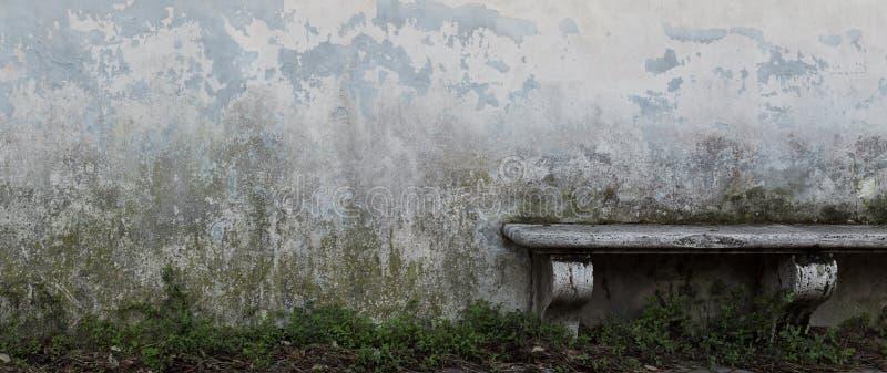 Banc en pierre antique devant le vieux mur gris avec s'émietter le pla photos stock