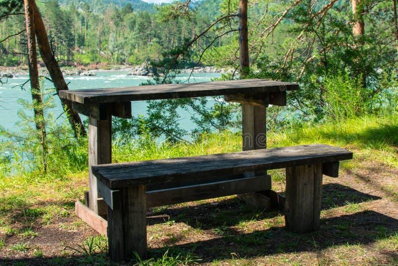 Banc et table par la rivière image stock