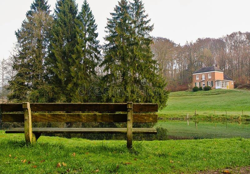 Banc par le lac et la Chambre sur les collines photo libre de droits