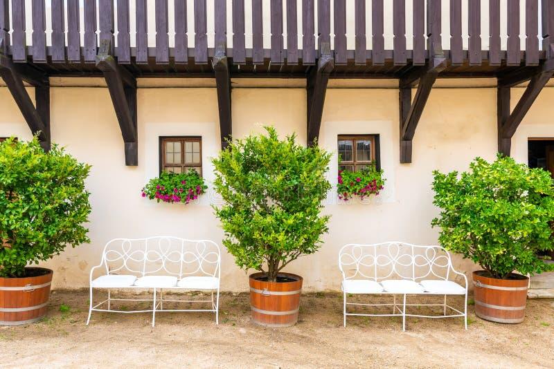 Banc sous la fenêtre avec la fleur Grands buissons à côté du banc avec les feuilles vertes fraîches Vieille construction individu images libres de droits