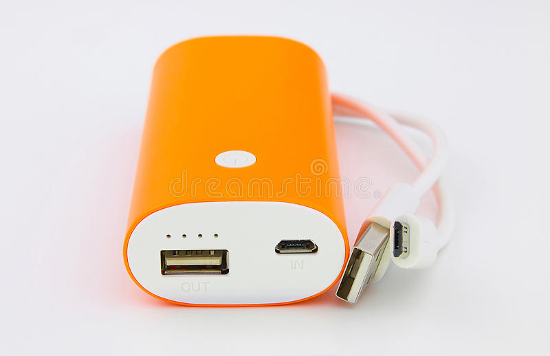 Banca arancio di potere e cavo di USB in--fuori fotografia stock