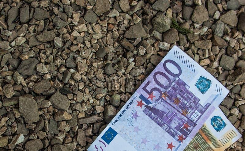 Banca-carte dai valori nominali cinquecento e duecento euro che si trovano sulle pietre immagini stock