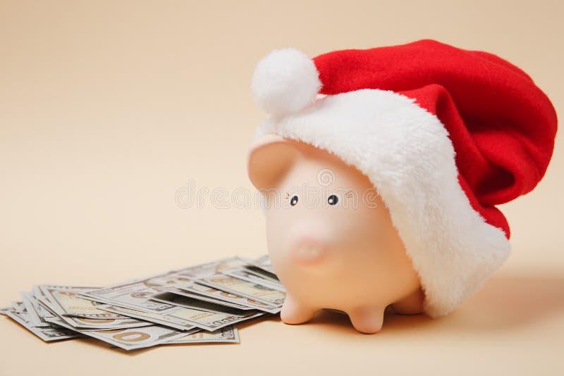 Banca dei soldi di porcellino con il mazzo del cappello di Natale di denaro contante delle banconote dei dollari su fondo beige S immagini stock libere da diritti